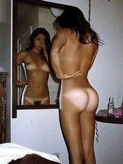 Tanned beauty nude in front of mirror