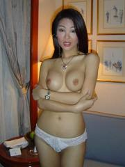 Pretty asian wife strips and spreads